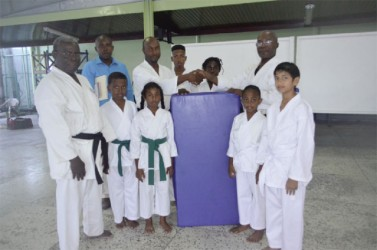 Lennox Brummell (third left) hands over one of the mats to Sensei Winston Dunbar in the presence of members of the  GWRKA.