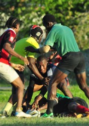 Some of the national ruggers going at it during one of the warm up games yesterday at National Park rugby field. (Orlando Charles photo)