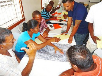 Participants pour over a map during the entry level training for prospectors in the extractive industry.