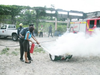 An AINLIM employee learning how to use the fire extinguisher
