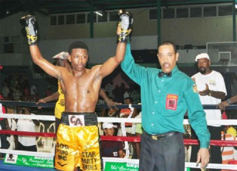 Champ! Referee Eon Jardine raises the hand of CABOFE featherweight, light welterweight and national featherweight and lightweight champion, Clive 'The Punisher' Atwell after his KO win over Jamaican, Glenroy 'Bumpy' Beckford. (Orlando Charles photo)