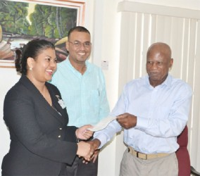 World Wildlife Fund (WWF), Country Manager – Dr. Patrick Williams (right) presents the $10M cheque to Guyana Forestry Commission, Head of Planning and Development – Pradeepa Bholanauth. Looking on is the Minister of Natural Resources and the Environment, Robert Persaud. (GINA photo)