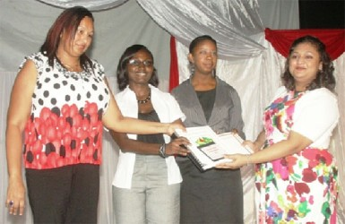 Minister of Education, Priya Manickchand (right), handing over the Portuguese syllabus to the teachers who assisted in preparing it. The teachers are (from left) Candida Williams – Head of Department, Modern Languages and Dianne Blenman of Queen's College and Malika Payne – Teacher, Bishops' High School. (GINA photo)