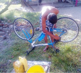 A young man cleaning his bicycle
