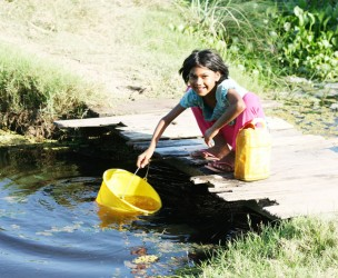 This young girl was fetching water from the  trench in front of her yard to complete her yard chores.