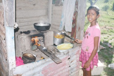 This young lady prepares pholourie and biganie for the family's dinner on  a fireside.