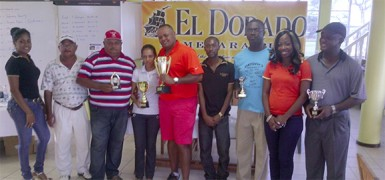 Troy Cadogan and Christine Sukhram, centre, show off the first and second place trophies following Saturday's El Dorado Classic golf tourney at the Lusignan Golf Club.