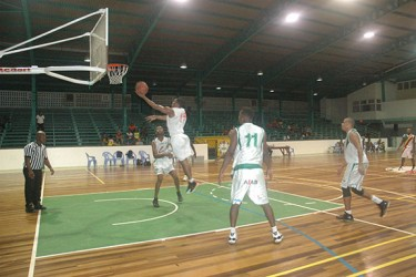 Shelroy Thomas (No.15) going up for a layup while Jahmal Henar (No.11) of Yellowbirds looks on.