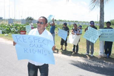 Former Toshao John Alfred bearing a placard at the protest yesterday. (Arian Browne photo