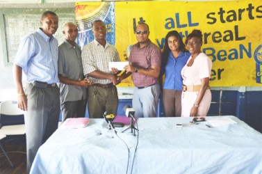 ANSA McAL Brands Coordinator Nigel Worrell (third from right) hands over the sponsorship cheque to GCA Treasurer Dennis Wilson with GCA President Roger Harper (left), GCA Chairman of Competitions Committee Shaun Massiah (second left), Deborah McNicholl (right) and ANSA McAL PRO Darshanie Yusuf.