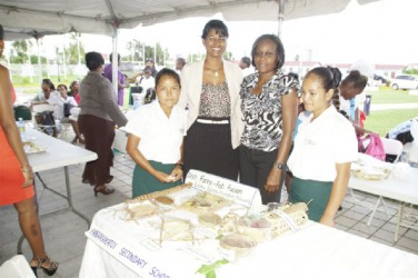 Two Paramakatoi students and their teacher pose with FAO's Angela Alleyne (second from right) while displaying their cassava delight at the Convention Centre