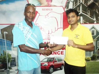Coach of the Roberts Champions Boxing Gym, Jeff Roberts receiving the sponsorship cheque from Hand-in-Hand's representative, Mark Samaroo yesterday.