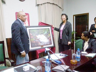 Parliamentary gift: Speaker of the National Assembly Raphael Trotman hands over a painting of Marshall Falls to Speaker of the Surinamese Parliament Dr. Jennifer Geerlings-Simons at Public Buildings yesterday.