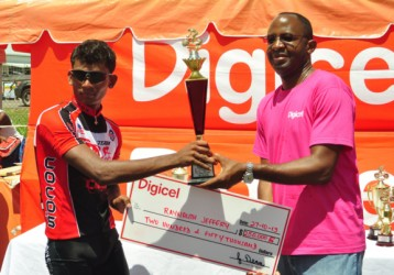 Raynauth Jeffrey receiving his spoils from Digicel's CEO, Gregory Dean. (Orlando Charles photo)