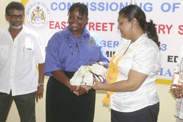 East Street Nursery's Head Teacher Belinda Cameron receives the keys to the new school building from Education Minister Priya Manickchand