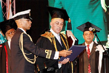 Aide-de-camp to the President, Lieut Commander Don Polo, left, assists President Anthony Carmona as he takes the Chancellor's Oath during the installation of UTT's chancellor at the O'Meara Campus. Looking on at right is Tertiary Education Minister Fazil Karim.