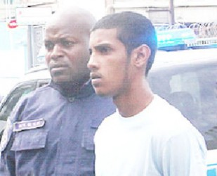 Murder accused Jonathan Johnson as he was escorted to the Port-of-Spain Magistrates Court yesterday.
