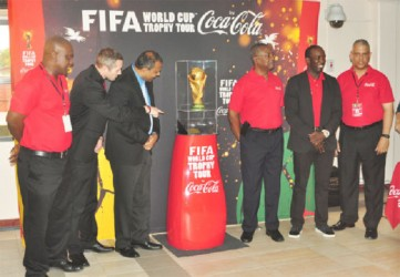 From left to right - GFF President Christopher Matthias, Coca-Cola representative Brad Ross, Minister of Culture, Youth and Sport, Dr. Frank Anthony, Banks DIH Limited Marketing/Co-Managing Director George McDonald, FIFA Ambassador Dwight Yorke and Banks DIH Limited Sales and Marketing Executive Carlton Joao pose with the FIFA World Cup Trophy. (Orlando Charles photo)