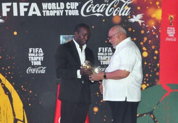 Former Trinidad and Tobago Captain and now FIFA Ambassador, Dwight Yorke, presenting a special gift to President, Donald Ramotar. (Orlando Charles photo)