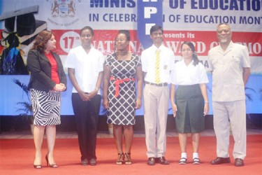 Prime Minister Samuel Hinds (right), and Minister of Education Priya Manickchand (left) with the students who the Government Information Agency said received a scholarship each at the behest of President Donald Ramotar; (from left) CAPE Students Melodie Lowe and Jonelle James and CSEC top awardees, Yogeeta Persaud and Cecil Cox. (GINA photo)