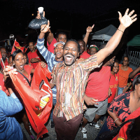 People's National Movement (PNM) Senator Fitzgerald Hinds celebrates with party supporters last night on his arrival at Balisier House in Port of Spain.