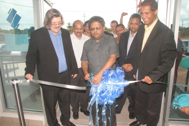 Minister of Finance Dr Ashni Singh cutting the ribbon. He is flanked by John Alves (left) and Nigel Baptiste. (GINA photo)