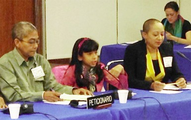 Daria Nicholson (centre) presenting at the hearing, flanked by Karen De Souza (left) of Red Thread and her mother Zenita Nicholson (right) of SASOD