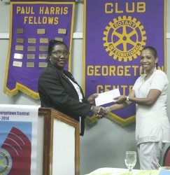 Georgetown Central Rotary Club President Judy Semple-Joseph (left) receives the cheque from Courts representative Molly Hassan.