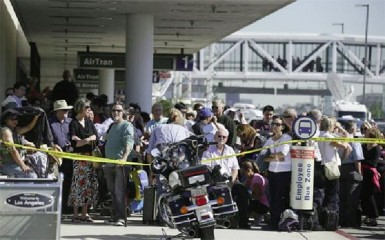 Delayed passengers stand behind a police cordon after a shooting incident at Los Angeles airport (LAX), November 1, 2013. REUTERS/Lucy Nicholson