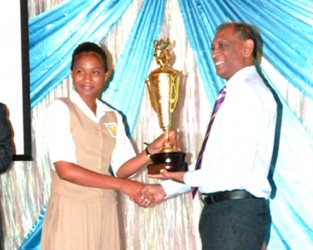 Minister of Agriculture, Dr Leslie Ramsammy presenting the overall award for the Best Pesticide Awareness Corner in a secondary school to a student of the Corentyne Comprehensive High School. (GINA photo)