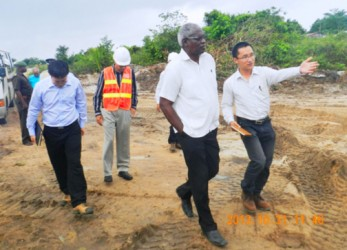 Minister of Works Robeson Benn on a tour of the runway extension works on Thursday.