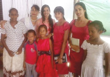 Proud mom Devika Persaud (second left) poses with her daughters and the recipients of the hamper they donated