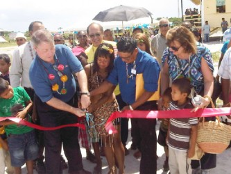 Cutting of the ribbon to officially commission the Swan Community Development Housing Project are (from left) Patrick Rainey, a village youth, village leader James Domingo and Mrs. Rainey