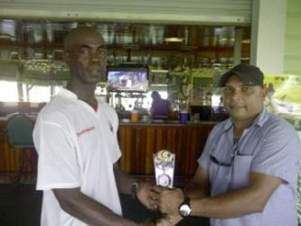 Man of the match Clive Grimmond receiving his award from owner of United Awning's Ray Persaud