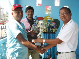 Clifton Phillips (R) hands over the trophies to BVA President Gregory Rambarran in the presence of Rollers Club President, Tony Rambarran.