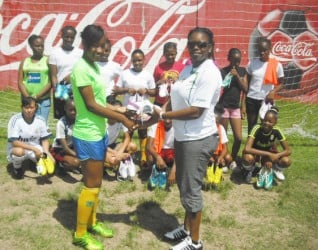 Vanessa Dickenson (right), President of the NAWF handing over the donated boots to club representative Aaliyah Stanley while other members look on.