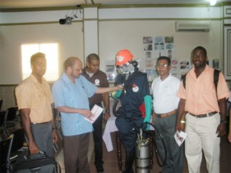 Minister of Health Dr Bheri Ramsaran (second from left) inspects one of the safety suits used by the VCS. In photo from left to right are Dr. Ahmad, VCS director Reyaud Rahman, VCS Chief Inspector Karanchand Krishnalall, and Dr. Dos Santos.