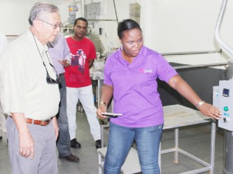 Sterling Products Limited (SPL) Chairman Dr Leslie Chin pays keen attention during a demonstration of operations at the Yo'great yogurt factory. (SPL photo)
