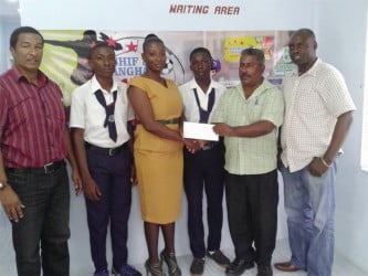 General Manager of the Bushy Park Sawmills, Patty Ramlall (second from right) hands over the sponsorship cheque to teacher and coach of the Uitvlugt Secondary School, Chevon Monchoir as students of the institution and co-founders of the K&S Organization, Kashif Muhammad (left) and Aubrey 'Shanghai' Major(right)  look on.