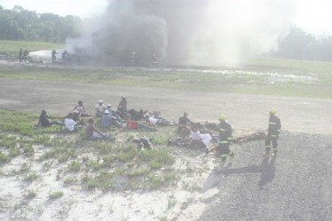 Ranks of the Guyana Fire Service extract 'passengers' from crash site to a safe area (GINA photo)