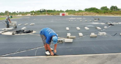 Workers laying the synthetic material on the track at the Leonora facility. (Orlando Charles photo)