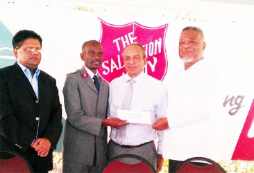 Prime Minister Samuel Hinds (right) handing over a cheque to Major Emmerson Cumberbatch of the Salvation Army at the launch of its Christmas Appeal 2013