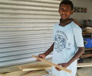Tariq Albert holds up a piece of wood he just cut