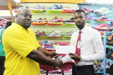 Giftland OfficeMax Public Relations Manager, Compton Babb hands over the stationery to Competitions Director of the National Schools' Championships  Ceon Bristol (left).