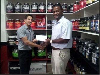 Organizing Secretary of the GAPF, Denroy Livan (right) receives a sponsorship cheque from Jamie McDonald to aid in Sunday's Senior Powerlifting Championships.