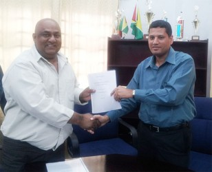 CEO of Natural Globe Inc Mohammed Osman (left) and Ministry of Local Government Permanent Secretary Collin Croal display the MOU.