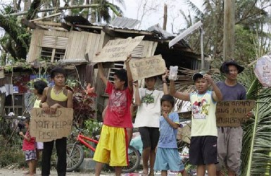 Children hold signs asking for help and food along the highway, after Typhoon Haiyan hit Tabogon town in Cebu Province, central Philippines November 11, 2013. (Reuters/Charlie Saceda)