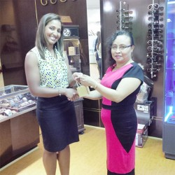 Myra Pierre-Moore (right) receiving her first prize of a diamond necklace, which she won in the United Women for Special Children (UWSC) fund-raising raffle, from a representative of King's Jewellery, which donated the prize.
