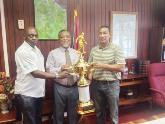 Prime Minister, Samuel Hinds (centre) presenting the championship trophy to co-founders of the K&S Organization yesterday at his office.