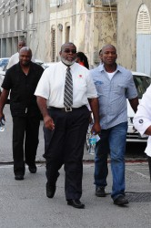 Journalist Sanka Price  (left front)  and Editor-in-Chief Roy Morris (left background) as they were led to the Magistrates' court.